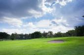 Golf course with sand bunker and green grass — Stock Photo