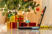 Laptop with gift box and christmas lights background — Stock Photo