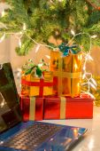 Laptop with gift box and christmas lights background — Stok fotoğraf