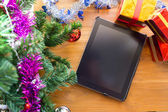 Black tablet on table wood with christmas decoration — Stockfoto