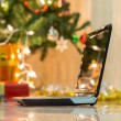 Laptop with gift box and christmas lights background — Stock Photo #57782185