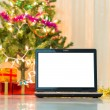 Laptop with gift box and christmas lights background — Stock Photo #57877939