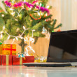 Laptop with gift box and christmas lights background — Stock Photo #57877951