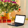 Laptop with gift box and christmas lights background — Stock Photo #57877965