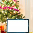 Laptop with gift box and christmas lights background — Stock Photo #58125431