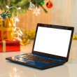 Laptop with gift box and christmas lights background — Stock Photo #58125439