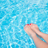 Woman legs with red nail in swimming pool — Stock Photo
