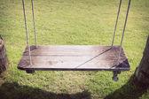 Playground swing hanging in green grass field — Stock Photo