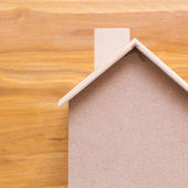 Small wood house model on brown wooden background — Stock Photo