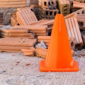 Construction cone in construction site with bricks — Stock Photo