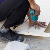 Carpenter hands using electric drill on wood at construction sit — Stock Photo