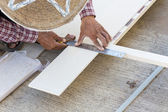 Carpenter hands using electric saw on wood at construction site — Stock Photo