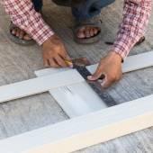 Stolarz za pomocą linijki narysować linię na boardzie drewna — Zdjęcie stockowe