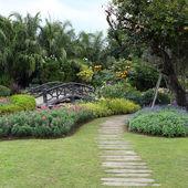 Landscape of floral gardening with pathway and bridge in garden — ストック写真