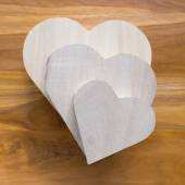 Wood box shaped heart on brown wooden background — Stock Photo