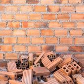 Mucchio dei mattoni in cantiere con il fondo del muro di mattoni — Foto Stock
