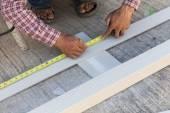 Carpinteiro, usando a régua para desenhar uma linha de marcação em uma placa de madeira — Fotografia Stock
