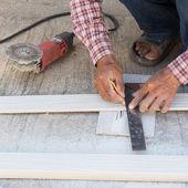 大工が木のボード上のマーキング線を描画する定規を使用して — ストック写真
