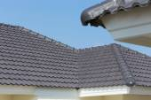 Black roof tiles on house with blue sky — Stock Photo