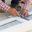 Carpenter using ruler to draw a line marking on a wood board — Stock Photo #65019695