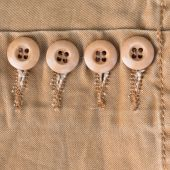 Design botton of brown shirt on fabric textile background — Stock Photo