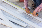 Carpenter using ruler to draw a line marking on a wood board — Stock Photo