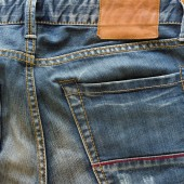 Blue jeans with back pocket and brown leather tag — Stock Photo
