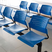 Customer waiting area with rows of blue seats in office — Stock Photo
