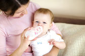 Mother holding a baby and feeding with a baby bottle — Stock Photo