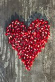Pomegranate seeds in heart shape — Stock Photo