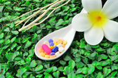Close up many colorful medicine tablet on the spoon with white flower and dried tree branch — Stock Photo