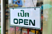 Open sign broad through the glass of window in rainy day with man holding umbrella reflected mirror. — Stock Photo