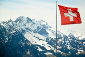 Flag of Switzerland on the Alps mountains landscape background. — Stock Photo
