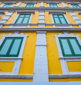 Green windows with yellow wall — Stock Photo