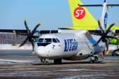 Пассажирский самолет ATR-72 компании UTair-Express на стоянке и хвост Airbus A320 компании S7 — Stock Photo