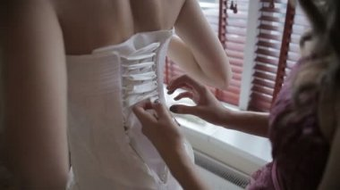 Lacing up a corset of a wedding dress — Stock Video