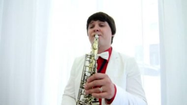 Man in festive costume plays saxophone — Stock Video
