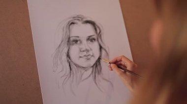 Artist paints a portrait of a beautiful woman — Vídeo de Stock