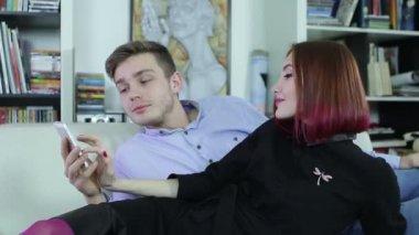 魅力的な若いカップルは一緒に自宅でリラックスし、スマート フォンを見て. — ストックビデオ
