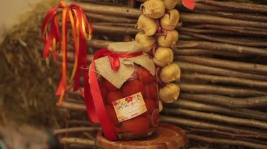 Jar with red tomatoes  on a background of  fence of twigs, hand made — Стоковое видео