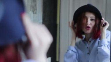 Женщина, носящая шляпу, применяя помаду косметики перед зеркалом — Стоковое видео