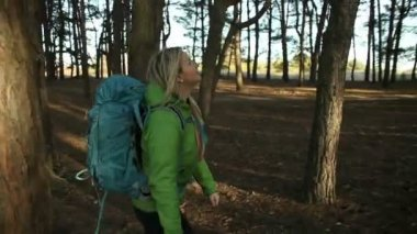 Hiker blonde woman walking hiking in forest with backpack. steadicam shot — Stock Video