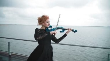 Young woman in black dress playing the violin on the wharf at the background of amazingly beautiful view of the river. Steadicam shot — Stock Video