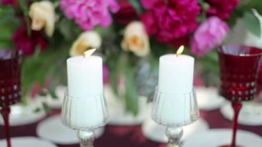Wedding table decor at the nature with lighted candles, close-up. Steadicam shot — Stock Video