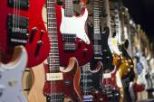 Many electric guitars hanging on wall in the sho — Stock Photo