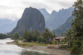Houses and mountains are located along the coast Nam song river Vang Vieng,Laos. — Foto de Stock