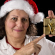 Mature Woman with Red Cap Pointing at Golden Gift — Stock Photo #52658381