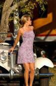 Professional Blonde Model Poses In Front of a Cool Car in a Pretty Dress — Stock Photo