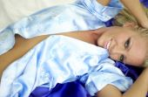 Light Blue Satin Robe - Dark Blue Satin Sheet - Sultry Sexy Bedroom Blonde — Stock Photo