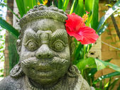 Guardian stone statue with a red hibiscus, Thailand — Stock Photo